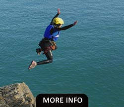 Woman jumping of a cliff while Coasteering North Wales