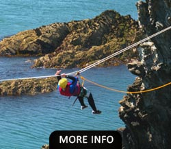 Man dangling on a rope while Sea Level Traversing on Anglesey